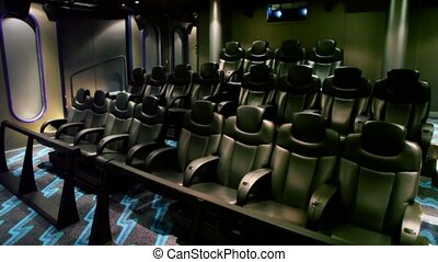 Few rows of black chair in small cinema, shown in motion