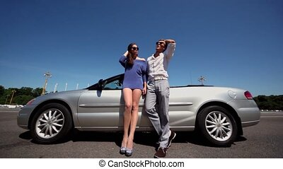 Young couple in sunglasses stand near cabriolet at summer day