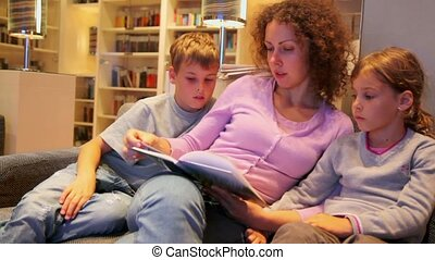 Two kids with mother sit on sofa and read book in small room