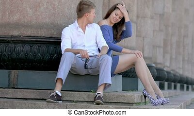 couple sit on steps near colonnade, boy talks with girl -...