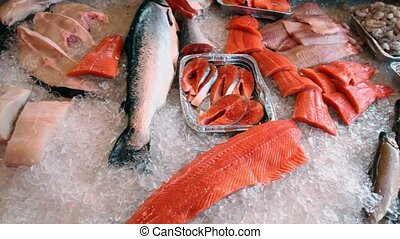 Red fish and other seafoods lay in ice, closeup view in...
