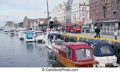 boats are in dock of coastal town Bergen, tourists walk...