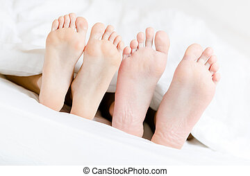 Close up of feet of the couple lying in bed-room