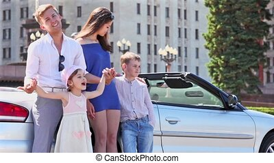 Young couple with two kids stand near cabriolet, boy hold...