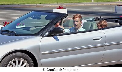 Young couple with two kids pass by in cabriolet with window...