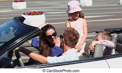 couple sit and smile in cabriolet and kids, then they ride away