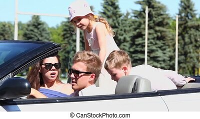 Young couple sit in cabriolet and two kids stand on back seats