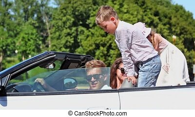 Students with two kids sit in cabriolet, boy closes window and wag his finger at kids behind, then they ride away