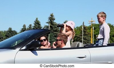 couple with kids sit in cabriolet, girl looks through binocular