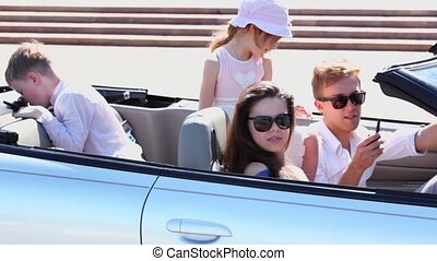 couple with kids sit in cabriolet, they talk by hand radio -...