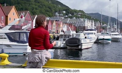 Woman sits on quay in dock with boats in coastal Bergen...