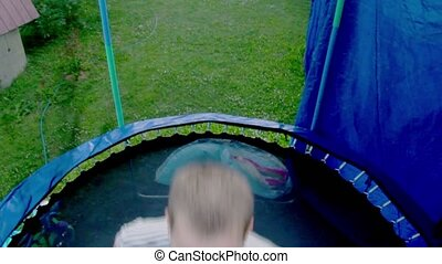 Young man jumps on trampoline with net around, closeup view...