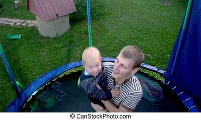 Young man hold child and jumps on trampoline with net around