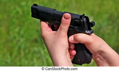 Woman holds black gun and shoots at background of grass