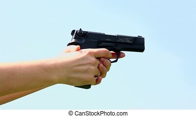 Womans hands with wedding ring on finger holds gun and...