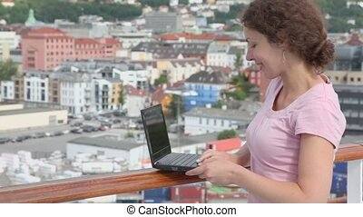 Woman types on netbook at deck of ship in port during cruise
