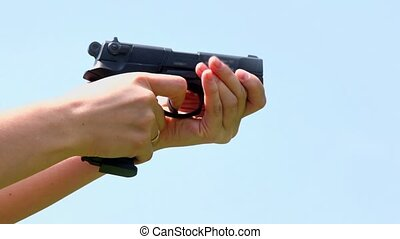 Woman holds gun and shoots with wedding ring on finger