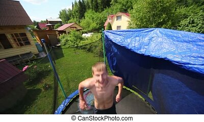 man jumps and raises hands to sides on trampoline - Young...