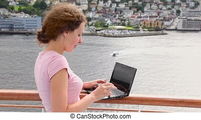 Woman pushes buttons on notebook at deck of ship in port...