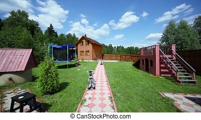Playground near path through yard of country house under sky...