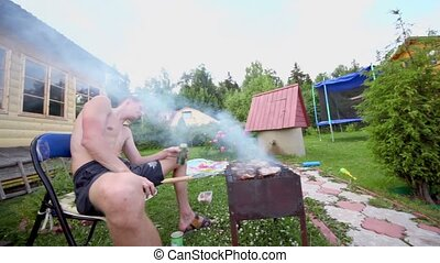 Man sit in smoke and makes kebab on grill near country...