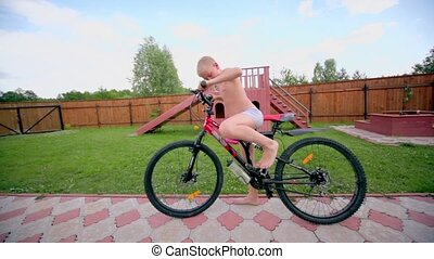 Boy in underpants ride on bike by road at homestead under...