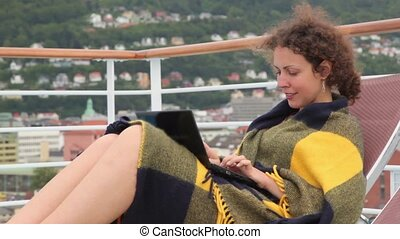 Woman sits and pushes buttons on netbook at deck of ship