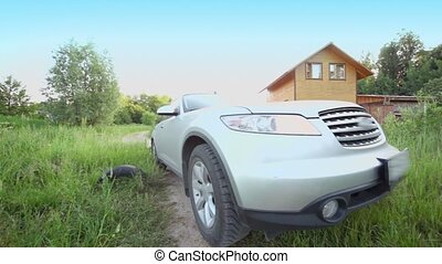 Car ride by path through grass field near country house and...