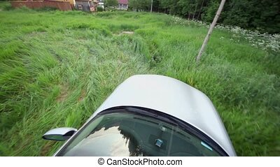 Car ride by grass field near country house at background of lake and village on other side