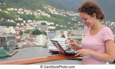 Woman types on netbook at deck of ship which floats in port