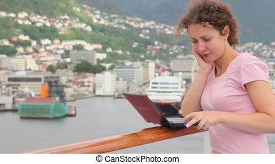 Woman pushes buttons on notebook at deck of ship which floats