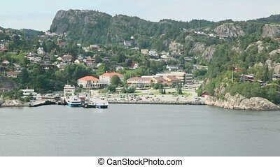 Few vessels on moorage at coastal town among forest on mountains, ship view during cruise