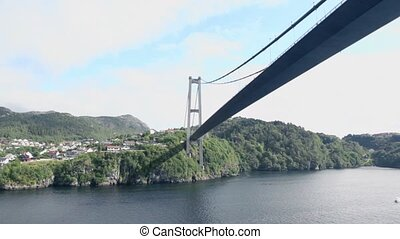 Huge pendant bridge at coast with houses among forest on...