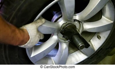 Hand spins car wheel mounted on stand, closeup view