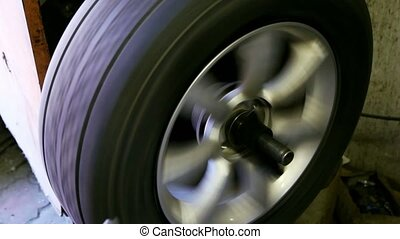 Man adjust balance of car wheel on special machine, closeup view