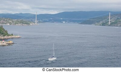 Yacht sail in bay with huge pendant bridge and town at coast...