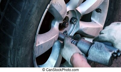 Man turn on wheel nuts with automatic tool, closeup view