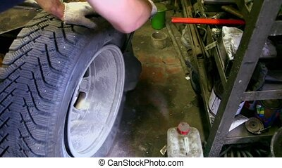 Man put off tyre from car wheel by special tool, closeup view