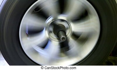 Car wheels spins, man stops it and fixates - Car wheels...