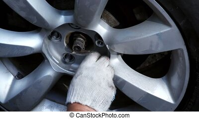 Hands in glove screw up nuts on car wheel, closeup view