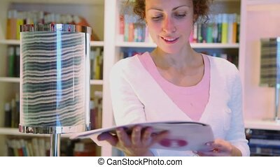 Woman reads magazine near lamp at cabin on ship during...