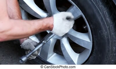 Man tight nuts on car wheel by cross screwdriver, closeup view