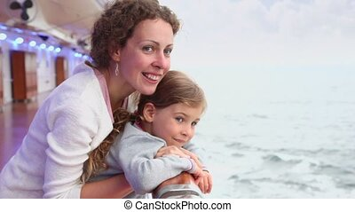 Mother with daughter stand on deck and admire seascape