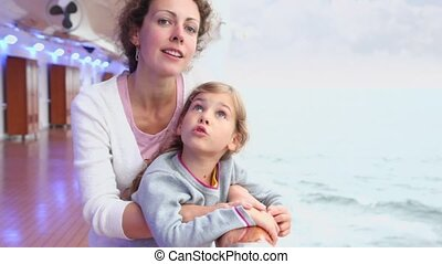 Mother with her daughter stand on deck near fence and watch seascape during cruise