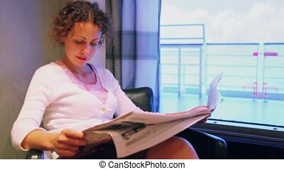 Woman sits in chair and reads newspaper at cabin on ship