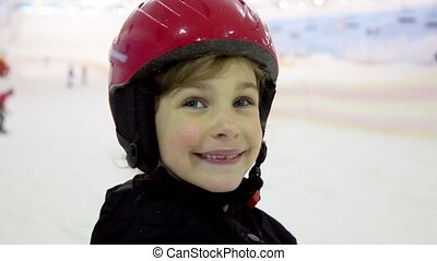 Little girl in red helmet looks and smiles closeup