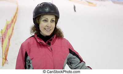 Young woman in helmet at background of snow slope