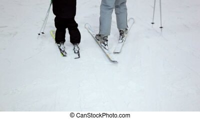 Mother with daughter move on ski, only leg are visible