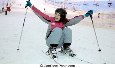 woman sits on ski and then rides away at background of ropeway
