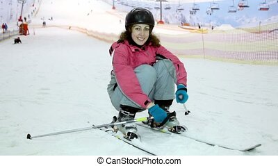 Young woman sits on ski at background of snow slope and ropeway